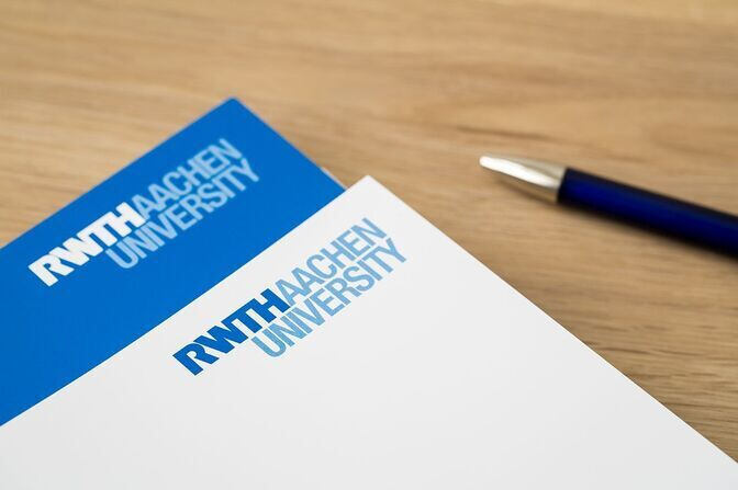Pen and paper with RWTH logo on a desk